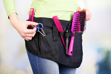 Woman hairdresser with tool belt on bright background