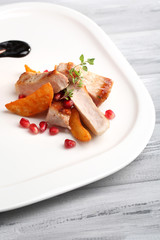 Grilled meat  with fried potato pieces and pomegranate seeds