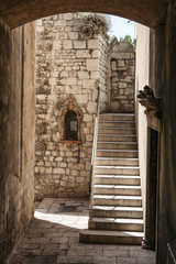 Old town passage with stairs and wall shrine in Sibenik, Croatia