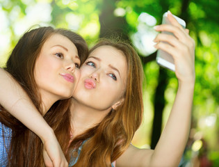 Teen friends taking photos with a smartphone. Selfie