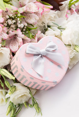 heart shaped gift box against a bouquet