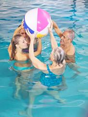 Senioren und Paar baden mit Wasserball