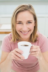 Relaxed woman having coffee in kitchen