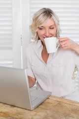 Mature woman drinking coffee while using laptop