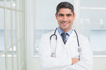 Smiling male doctor with arms crossed in hospital