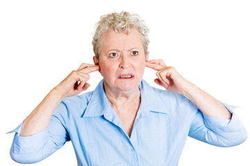 Loud noise. Angry displeased senior woman plugs her ears