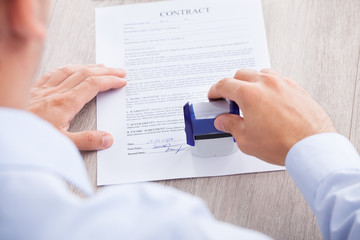 Businessman Stamping Contract Paper On Table