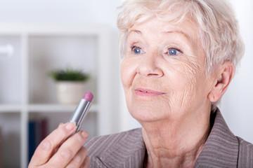 Elderly woman putting on lipstick
