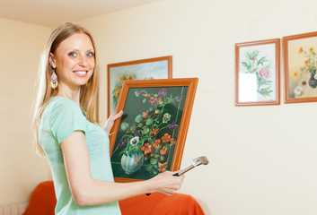 Happy woman hanging the  pictures