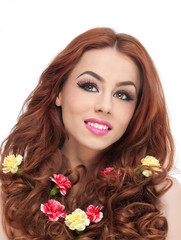 beautiful girl in studio with yellow and red carnations in hair