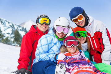 Five happy smiling friends with snowboards