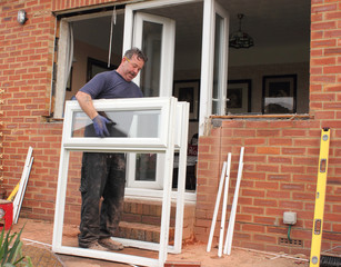 A Window fitter removing old windows in preparation for new ones