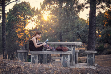 Young woman reading a book in the forest