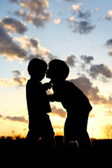Big Brother Kissing Baby Silhouette at Sunset