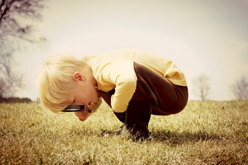 Young Child looking through Magnifying Glass