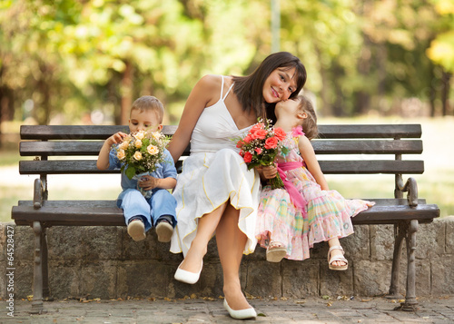 Two little children expressing love and affection to mommy.