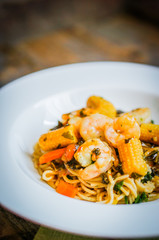 Italian pasta with shrimps and vegetables on wooden background