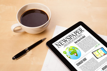 Tablet pc shows news on screen with a cup of coffee on a desk