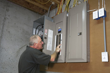Man standing next to fuse box in a basement