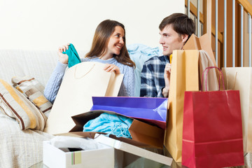 Happy woman and man with clothes and shopping bags