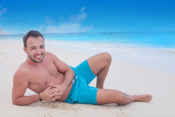 happy young man resting on the beach