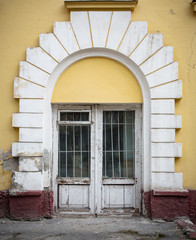 Low wooden window, with white around the arch windows and cracke