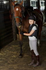 Horse and lovely equestrian girl in the stable