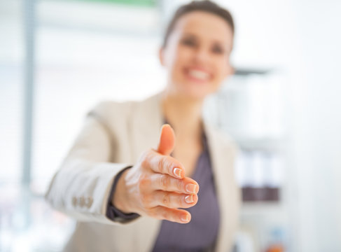 Closeup on happy business woman stretching hand for handshake