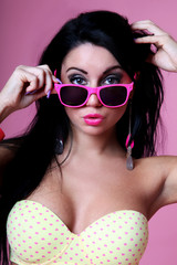 Sensual brunette with beachwear and sunglasses pink