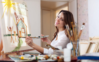Happy  woman paints home of dreams on canvas