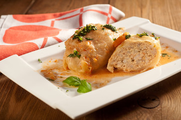 Closeup of stuffed cabbage rolls with tomato souce and herbs