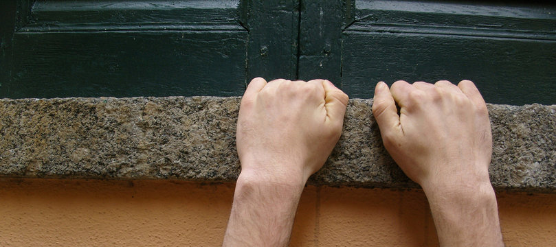 hands hanging from a ledge