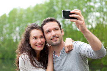Young couple taking selfie picture at the park