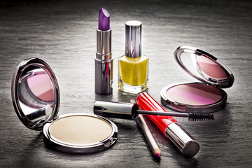 Cosmetics on black slate background