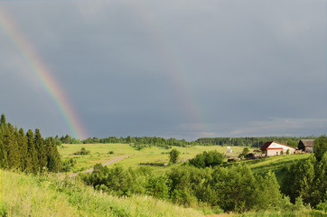 Rainbow in the dark sky in the summer evening