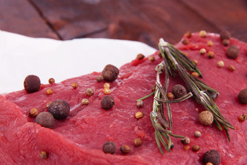 Raw beef meat with spices on paper on wooden background