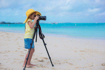 Little girl shooting with camera on a tripod during her summer
