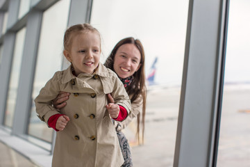 Mother and little daughter near the window at airport terminal