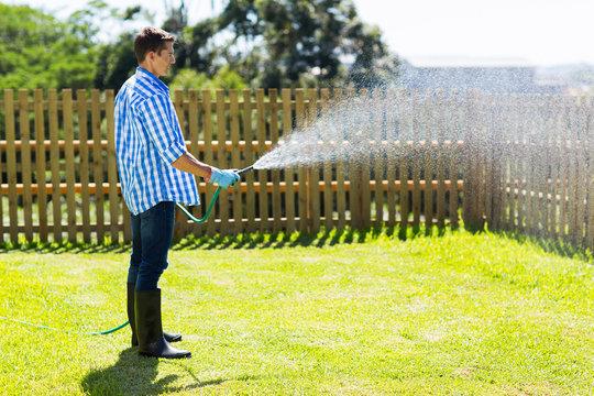 young man watering backyard lawn