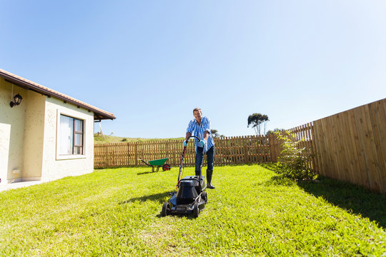 cheerful young man mowing lawn