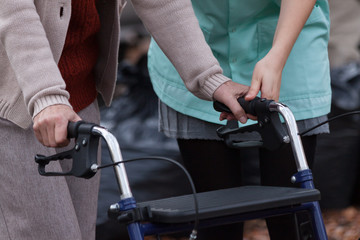 Nurse helping disabled lady with walker