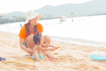 Daughter and mom playing on beach