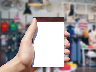 white blank vertical notebook in woman hand and shop background
