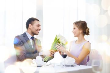 smiling man giving flower bouquet at restaurant