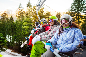 Four snowboarders sitting in elevator