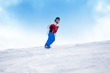 Man riding on the snowboard down mountain hill