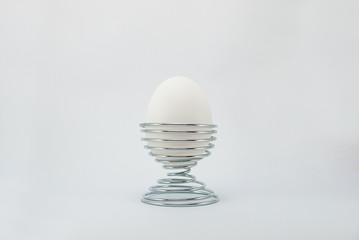 White egg on metal stand holder