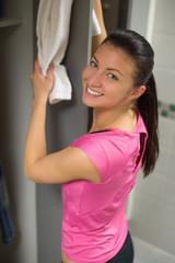 Woman placing towel on open locker door