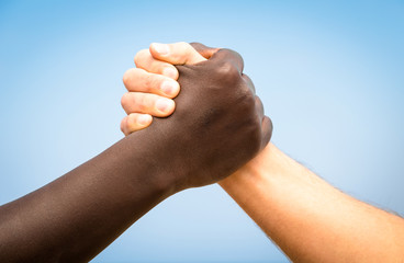 Black and white human hands shake - Handshake against racism