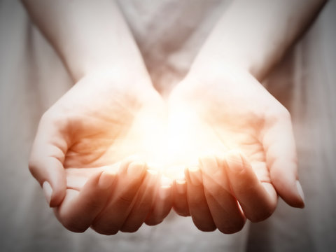 The light in young woman hands. Sharing, giving, protection